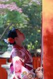 La ragazza giapponese nel supporto del vestito dal kimono ed il tessuto del fermo rope a suonare la campana per benedicono al san fotografie stock libere da diritti