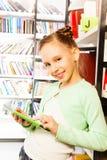 La ragazza gioca con la compressa vicino allo scaffale per libri in biblioteca Fotografia Stock Libera da Diritti