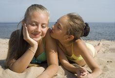 La ragazza gioca con la sabbia su una spiaggia Fotografia Stock Libera da Diritti