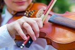 La ragazza gioca il violino, la mano della ragazza con il bow_ delle fiddle immagini stock libere da diritti