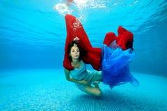 La ragazza gioca underwater al fondo dello stagno con un panno rosso e blu ed esamina la macchina fotografica Fotografia Stock Libera da Diritti