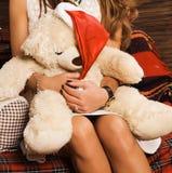 La ragazza giudica un giocattolo molle di un orso disponibile Fotografia Stock