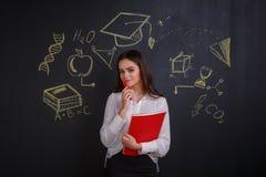 La ragazza giudica un indicatore e una cartella rossa, stanti accanto ad una lavagna con un'immagine di scienza Fotografia Stock Libera da Diritti