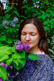 La ragazza gode dell'odore meraviglioso del lillà i fiori in mani sta stando vicino all'albero lilla di fioritura Immagine Stock