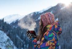 La ragazza gode delle cadute della neve La giovane donna in una forma tricottata sta bevendo il tè nella foresta durante precipit immagini stock