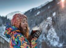 La ragazza gode delle cadute della neve La giovane donna in una forma tricottata sta bevendo il tè nella foresta durante precipit fotografia stock libera da diritti