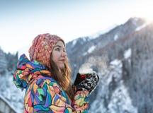 La ragazza gode delle cadute della neve La giovane donna in una forma tricottata sta bevendo il tè nella foresta durante precipit immagini stock libere da diritti