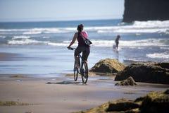 La ragazza gode di di ciclare il viaggio lungo la costa del Pacifico immagine stock
