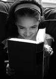 La ragazza gode di di leggere Fotografia Stock