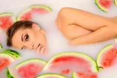 La ragazza gode di un bagno con latte e l'anguria. fotografia stock
