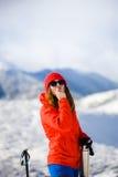 La ragazza gode di un rossetto igienico nelle montagne Immagini Stock
