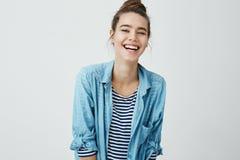 La ragazza gradisce gli scherzi divertenti Bello studente astuto con l'acconciatura del panino che trema dalla risata, sorridente Fotografie Stock