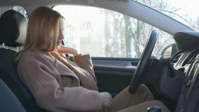 La ragazza in grande aspettativa chiude la porta di automobile e pancia di segno che si siede nell'automobile in lampadina archivi video