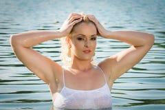 La ragazza graziosa in acqua esamina la macchina fotografica Immagine Stock Libera da Diritti