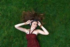 La ragazza graziosa ascolta musica in cuffie che si trovano sull'erba Fotografia Stock Libera da Diritti