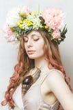 La ragazza graziosa calma con la lumaca ed il fiore incoronano Immagine Stock