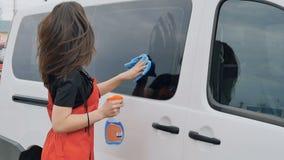 La ragazza graziosa in camici arancio lucida la finestra di automobile video d archivio