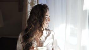 La ragazza graziosa in camicia da notte beve una tazza di caffè vicino alla finestra in 4K stock footage