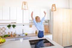 La ragazza graziosa cammina nella cucina e negli allungamenti, godenti della mattina c fotografie stock libere da diritti