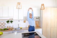 La ragazza graziosa cammina nella cucina e negli allungamenti, godenti della mattina c immagini stock libere da diritti