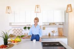 La ragazza graziosa cammina nella cucina e negli allungamenti, godenti della mattina c fotografia stock