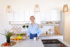 La ragazza graziosa cammina nella cucina e negli allungamenti, godenti della mattina c Fotografia Stock Libera da Diritti