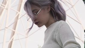 La ragazza graziosa in capelli di carezza di vetro sotto i ferris spinge dentro il parco di amusment stock footage