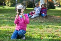 La ragazza graziosa che fa l'immagine con il telefono, il padre, il fratello del anb della madre è su fondo fotografia stock