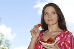 La ragazza graziosa che si distende sul balcone e mangia fresco rosso Fotografia Stock
