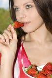 La ragazza graziosa che si distende sul balcone e mangia fresco rosso Fotografia Stock Libera da Diritti