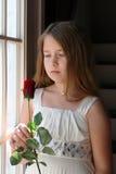 La ragazza graziosa che tiene un rosso è aumentato vicino alla finestra Fotografie Stock Libere da Diritti