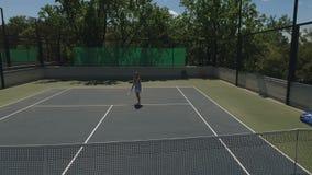 La ragazza graziosa colpisce le palle al campo da tennis video d archivio