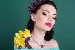 La ragazza graziosa con i fiori porpora si avvolge in capelli Fotografia Stock