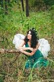 La ragazza graziosa con l'angelo traversa nella foresta Immagine Stock