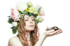 La ragazza graziosa con la lumaca ed il fiore incoronano sulla testa Fotografia Stock Libera da Diritti