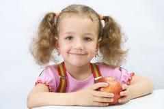 La ragazza graziosa con una mela Fotografia Stock