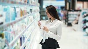 La ragazza graziosa in cosmetici compera sceglie crema, esamina le merci, legge gli ingredienti