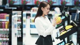 La ragazza graziosa in cosmetici compera sceglie il gel e la pezzuola per lavare della doccia