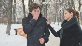 La ragazza graziosa dà uno spruzzo di naso ad un tipo di starnuto nel parco dell'inverno archivi video