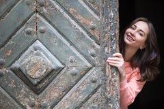 La ragazza graziosa dà una occhiata a fuori da dietro il vecchio portone di legno Immagini Stock Libere da Diritti