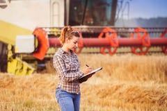 La ragazza graziosa dell'agricoltore tiene una contabilità del raccolto nella cartella Fotografie Stock