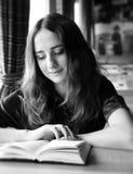 La ragazza graziosa dello studente legge un libro in un caffè fotografia stock libera da diritti