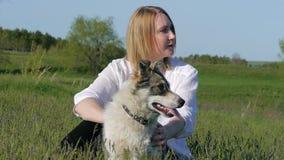 La ragazza graziosa gioca con un cane sull'erba dal lago video d archivio