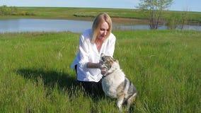La ragazza graziosa gioca con un cane sull'erba tramite il movimento lento felice del cane di sorriso di emozioni dell'amico degl archivi video