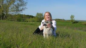 La ragazza graziosa gioca con un cane sull'erba tramite il movimento lento felice del cane di sorriso di emozioni dell'amico degl stock footage