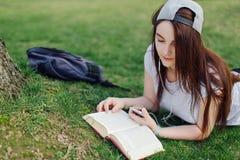 La ragazza graziosa ha letto il libro ed ascolta musica al parco Fotografia Stock