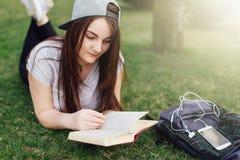 La ragazza graziosa ha letto il libro ed ascolta musica al parco Immagine Stock