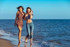 La ragazza graziosa ha un divertimento con la sua amica sulla spiaggia Immagini Stock