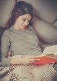 La ragazza graziosa legge un libro al sofà Immagine Stock