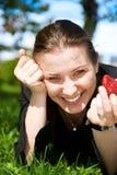 La ragazza graziosa mangia la fragola rossa del frash su verde Fotografie Stock Libere da Diritti